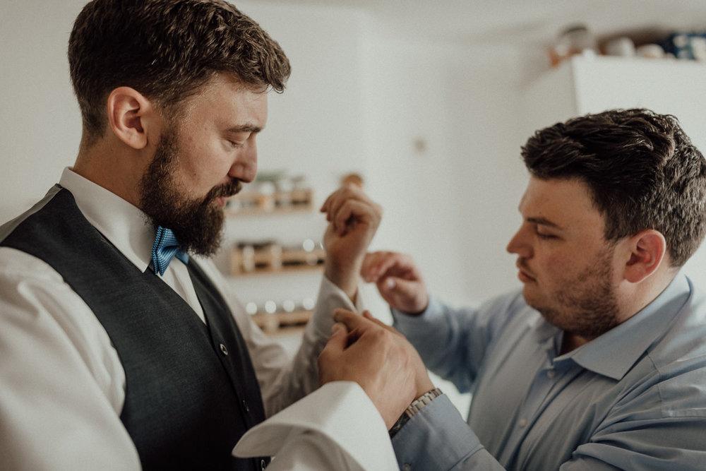 Bräutigam schließt Manschettenknöpfe beim Getting-Ready