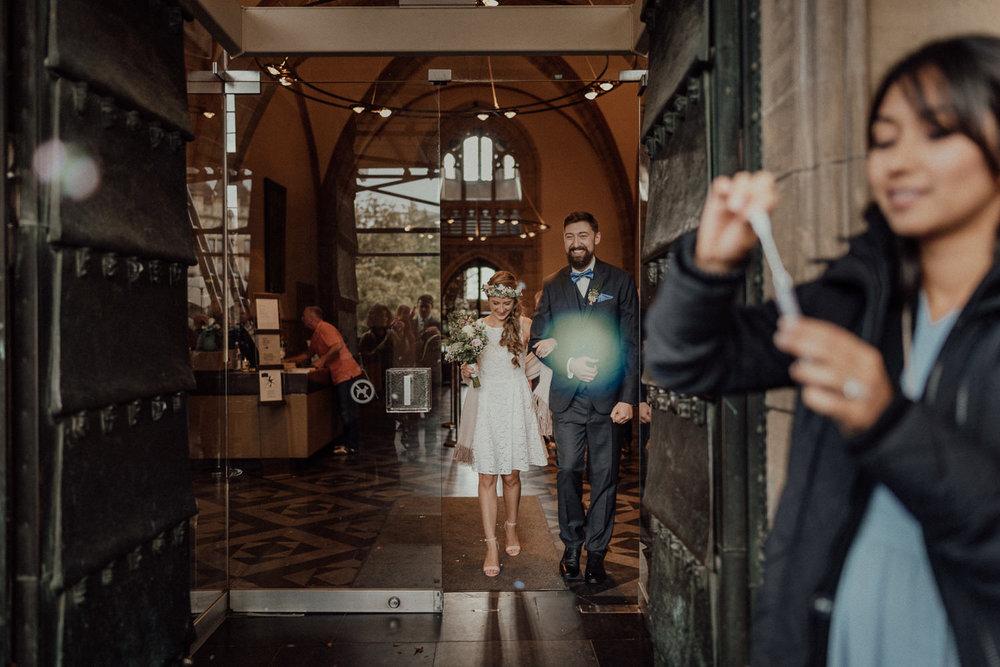 Überglückliches frisch vermähltes Brautpaar verlässt den weißen Saal in Aachen
