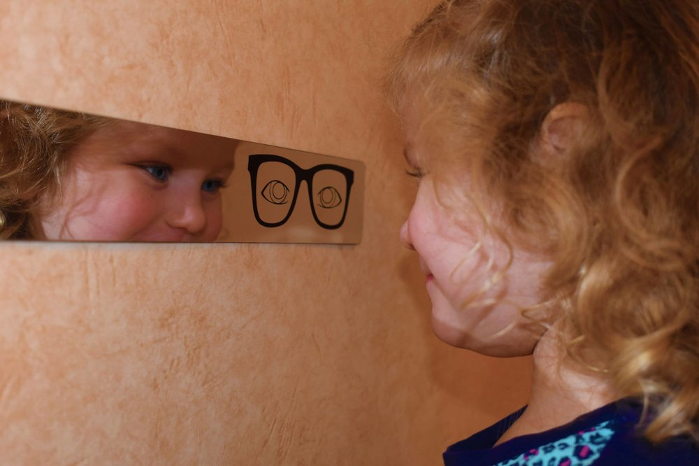 Eyeline child proof mirror with little girl playing front of it.