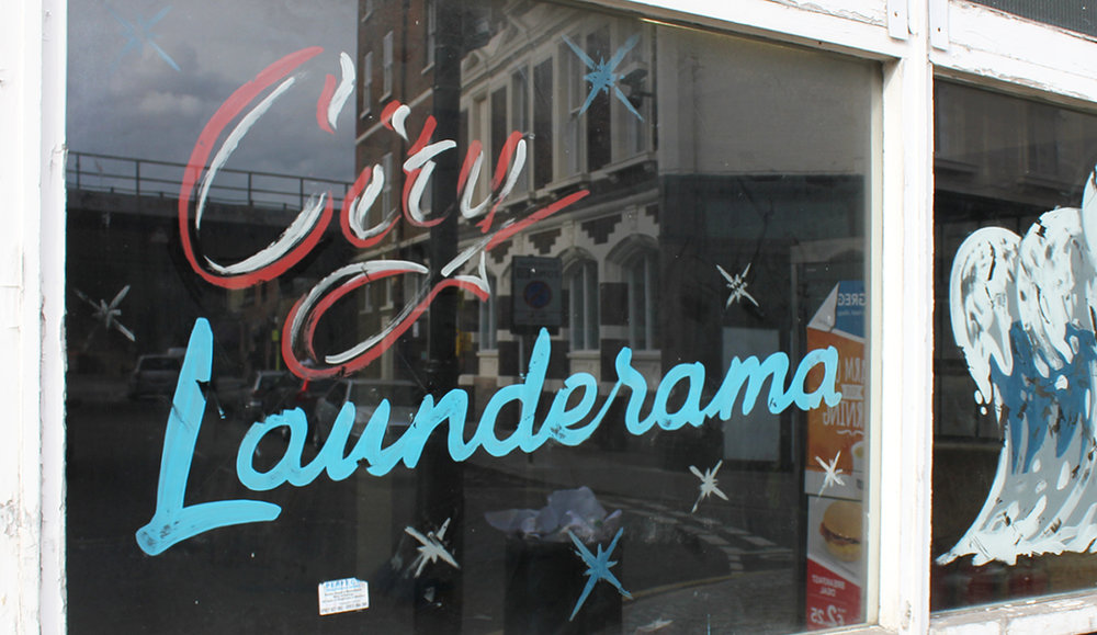 Hand drawn lettering and window design for run down laundrette shopfront, hand painted and aged.