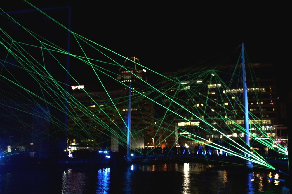 """Installation:  OUR HOUSE by Tom Dekyvere (Belgium)   """"Using an illuminated nylon fabric across the suspension bridge of Piers 3 & 4, OUR HOUSE illustrates togetherness and collaboration in contrast with nature and technology through the metaphoric symbols of sound and vision."""""""
