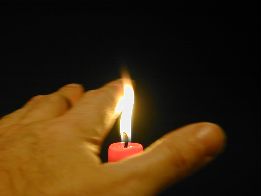 I managed to photograph my own left hand performing another party trick. If you spread your fingers widely like this, it is possible to float your hand through a candle flame surprisingly slowly without being burnt.  This cools the flame so much that a small wisp of black, unburned smoke particles puffs up between each pair of fingers.