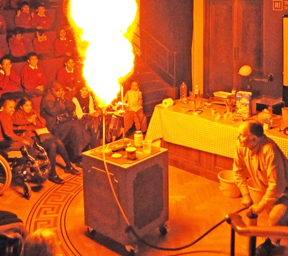 Notice, in the previous paragraph, how little effort Faraday makes to discourage his audience of children from experimenting at home with gunpowder!  Faraday's next demonstration uses lycopodium powder, an extremely fine powder consisting of club-moss spores.  The photograph, taken at the Royal Institution, shows my own version of the same demonstration, but instead using custard powder which is basically cornflour. I have presented my Exploding Custard show to children at the Royal Institution a number of times, standing exactly where Michael Faraday stood.