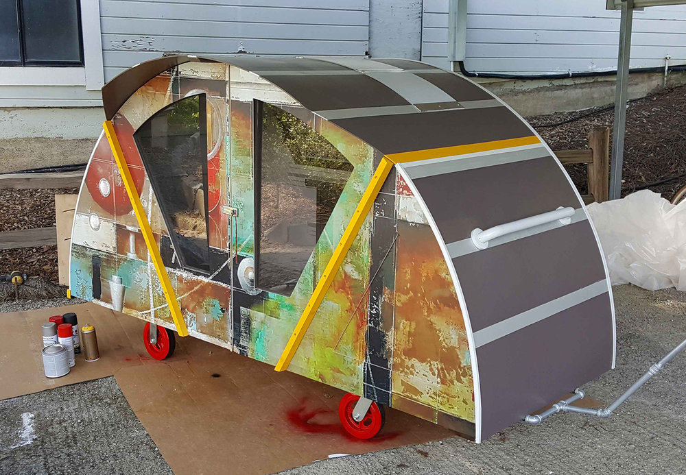 The finishing touches on 'Dorothy' the mobile shelter. Vinyl graphic shell featuring my painting 'Urban Fabric'. Red wheels meant to represent Dorothy's ruby slippers. Yellow accents meant to represent the yellow brick road.