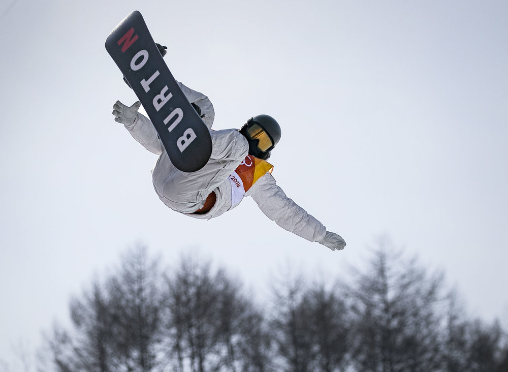Two time Olympic champion, halfpipe snowboarder Shaun White, reaches for his second jump at Phoenix Snow Park, PyeongChang, Feb. 13, for his second run scoring a 98.50, leading his way to the halfpipe finals. White will compete tomorrow against 11 other snowboarders to hold his position, in hopes to win his third Olympic gold medal.