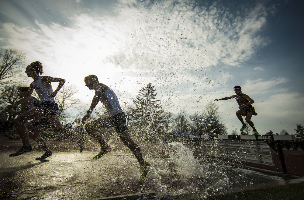 Runners charge through a pool during the 3,000 Meter Men's Steeplechase race, April 13 at Ball State University Track during a 12 school MAC dual track meet.  Photos for Ball State Photo Services
