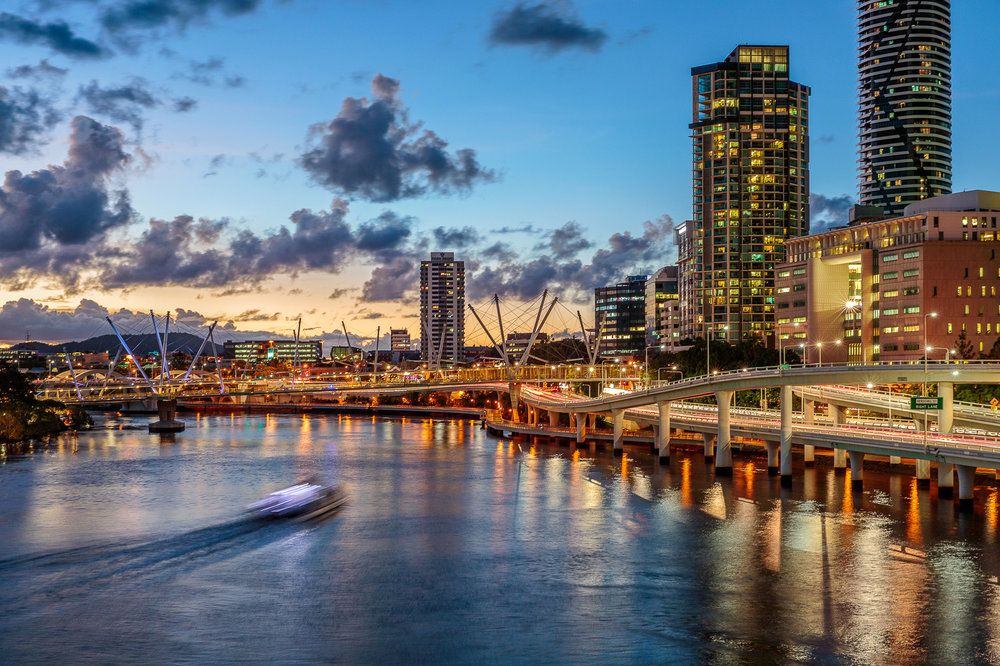 Evolution Apartments hotel exterior and Brisbane River at dusk