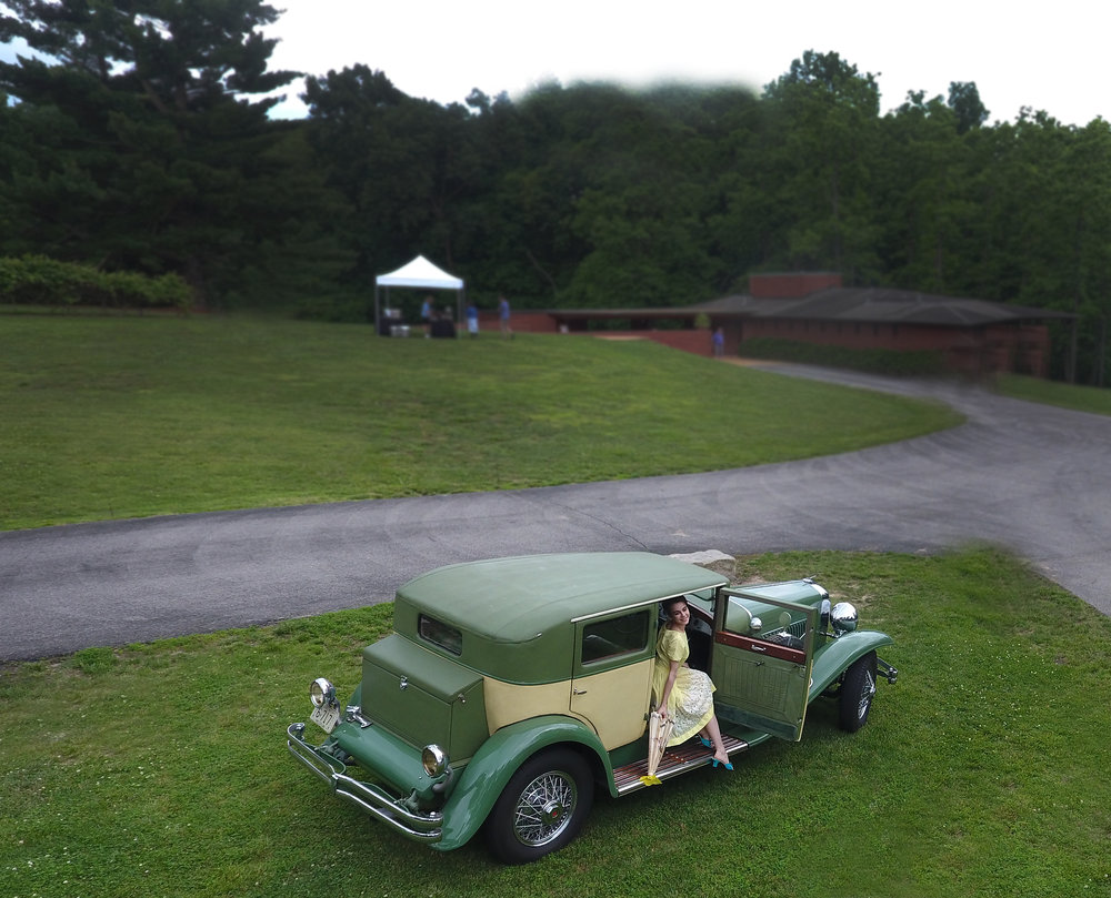 Aerial photo of a lovely model stepping out from Richard Quick's 1929 Duesenberg J Weymann Sedan with Frank Lloyd Wright designed home in the background.