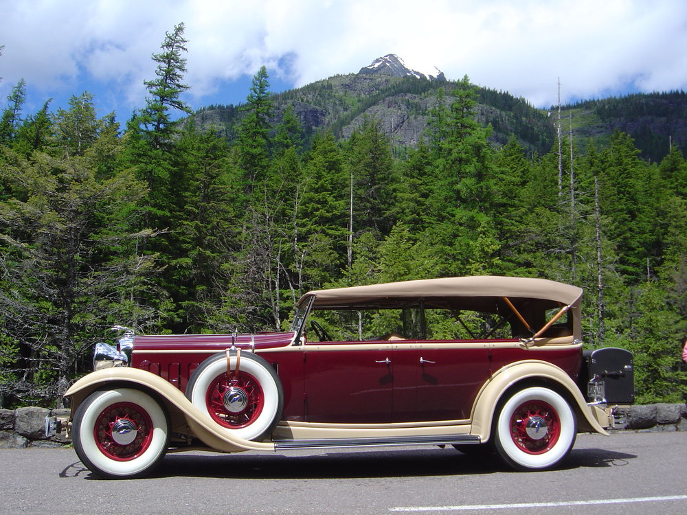 Majestic snow capped mountain setting frames a 1932 Lincoln KB Touring