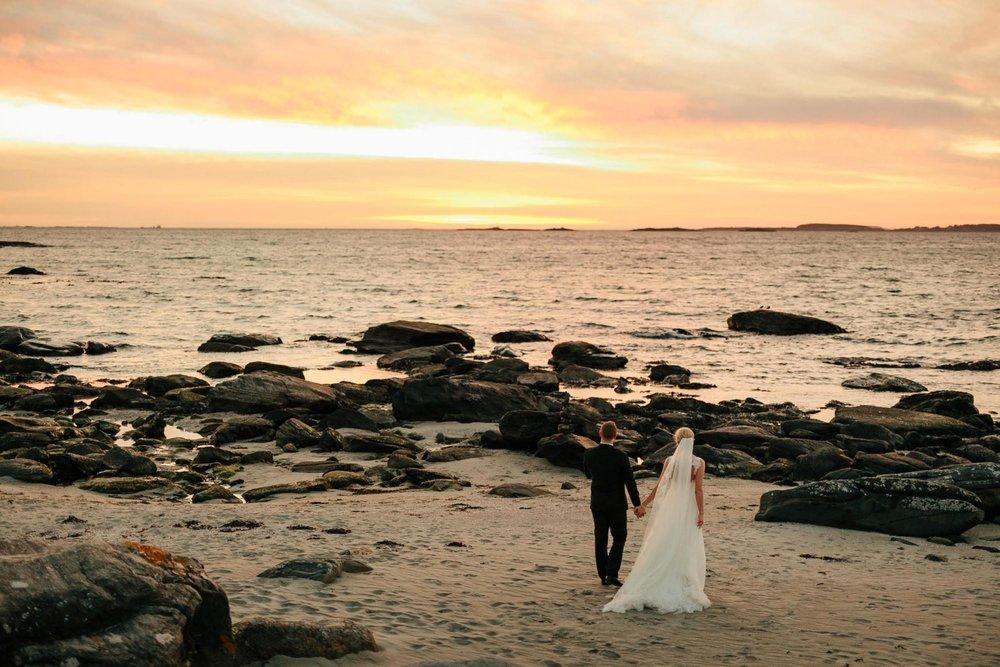 Bryllupsbilde på stranden med solnedgang i bakgrunnen