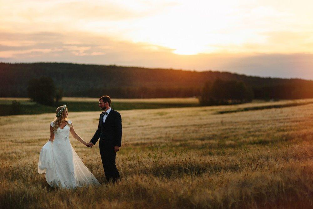 Brudepar i åkerlandskap med solnedgang i bakgrunnen