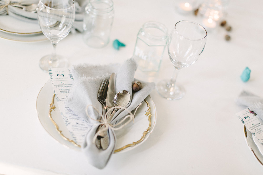 Duken er droppet og de hvite trebordene er dekket med forskjellige tallerkener og bestikk og hjemmelagde linservietter. Foto:  Moment Studio