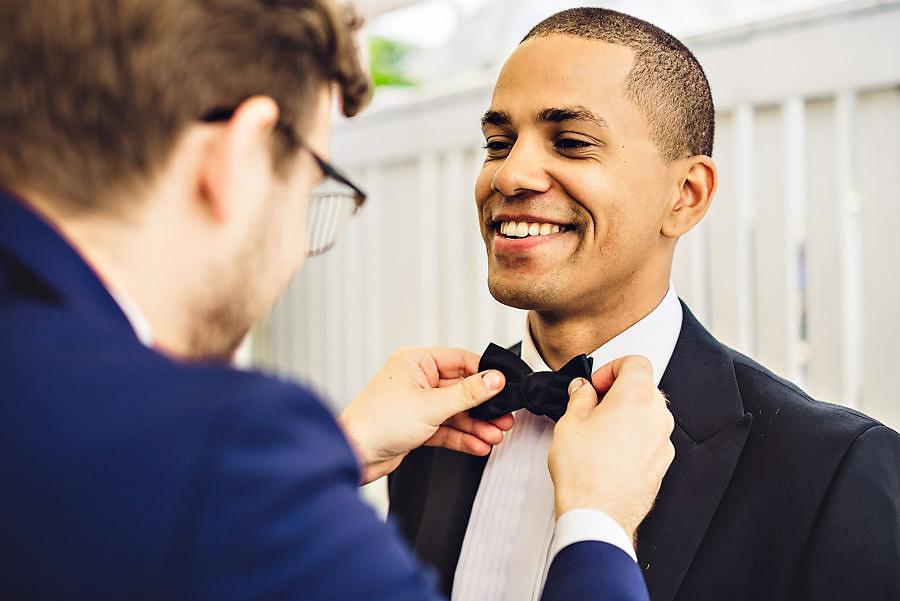 forlover retter på sløyfa til brudgommen bryllupsfotograf stav