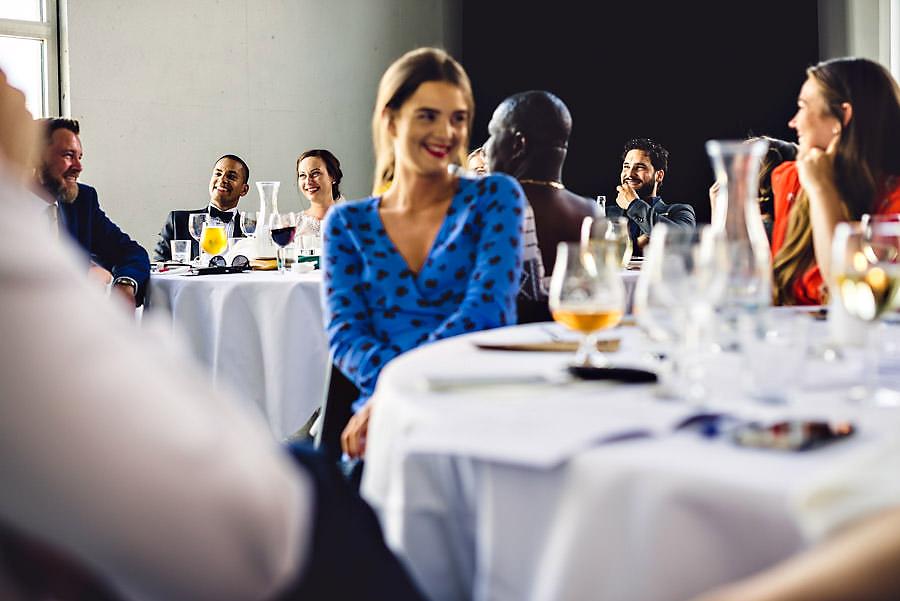 brudeparet og gjester ler under talene i bryllup på tou scene i