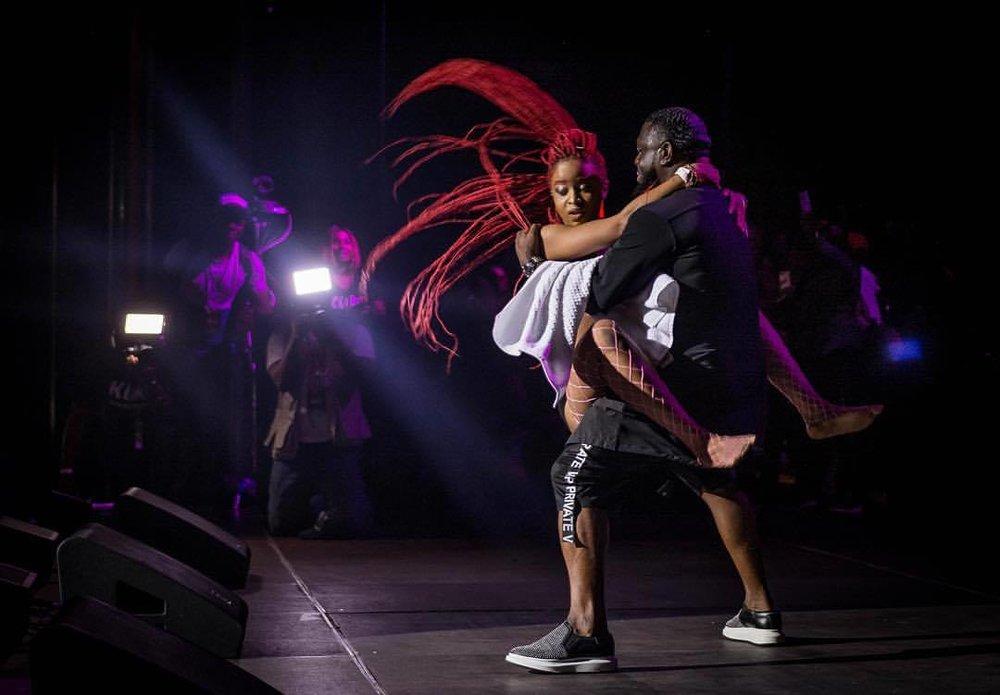 Timaya daggering dancer on stage.