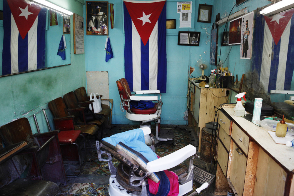 """Young Cuban men could be described as """"dandies"""", as they strut peacock-like around the streets. They take great pride in their hairstyles, with names like """"El Yonki"""" and """"Tiburon"""", that they get sculpted and fashioned in barbershops all over Havana, sometimes late into the night"""""""