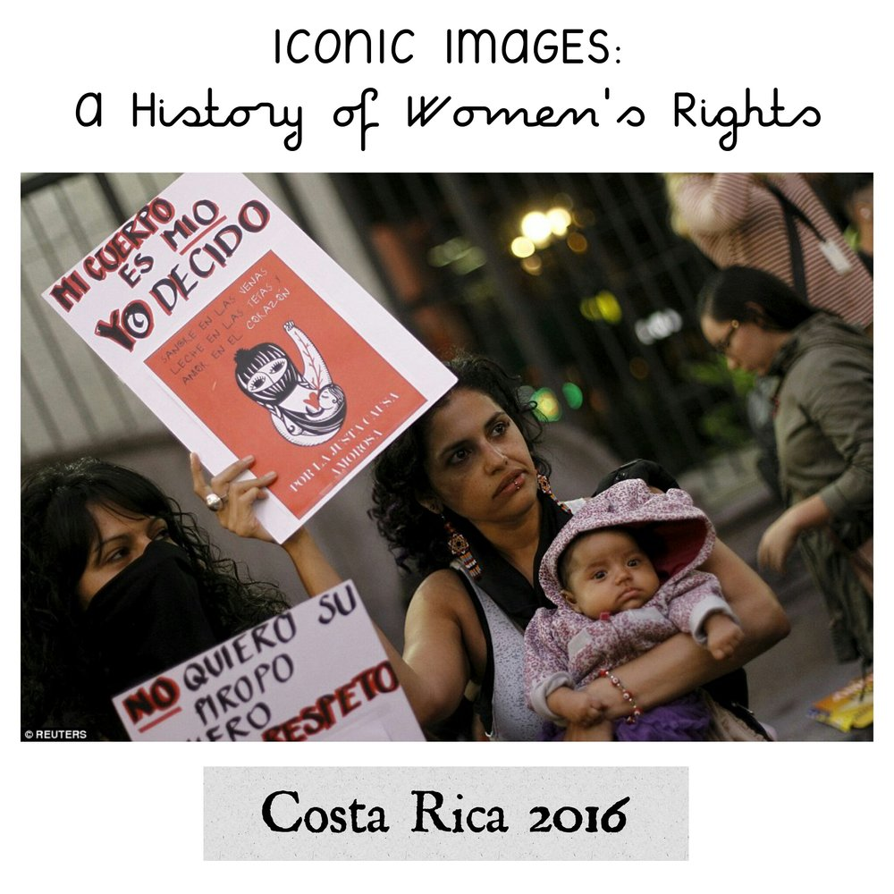 - A woman holds up her baby and a sign that reads