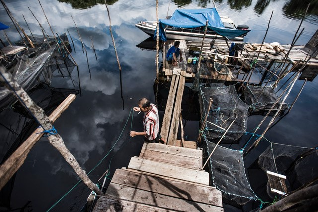 Villagers setting up and checking fish nets in a river in Central Kalimantan.  Because of canals draining the land, many of these rivers, and thus these communities are threatened by low water levels.    Photo was taken as part of an exhibition on GAMBUT for COP-22. Photo by Kadir van Lohuizen (c).