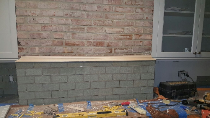 Custom moulding integrating existing brick work with new backsplash in a kitchen