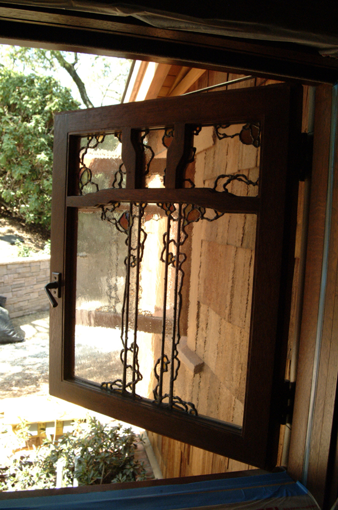 Kitchen casement window with a stylized rose vine design.