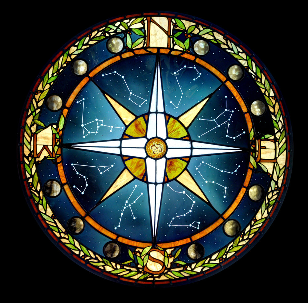 Inspired by the finest traditions of American Art Glass, this compass window is made of custom night sky glass that has wheel-cut constellations, hand-painted moon phases and a hand-blown iridescent nebula centerpiece.