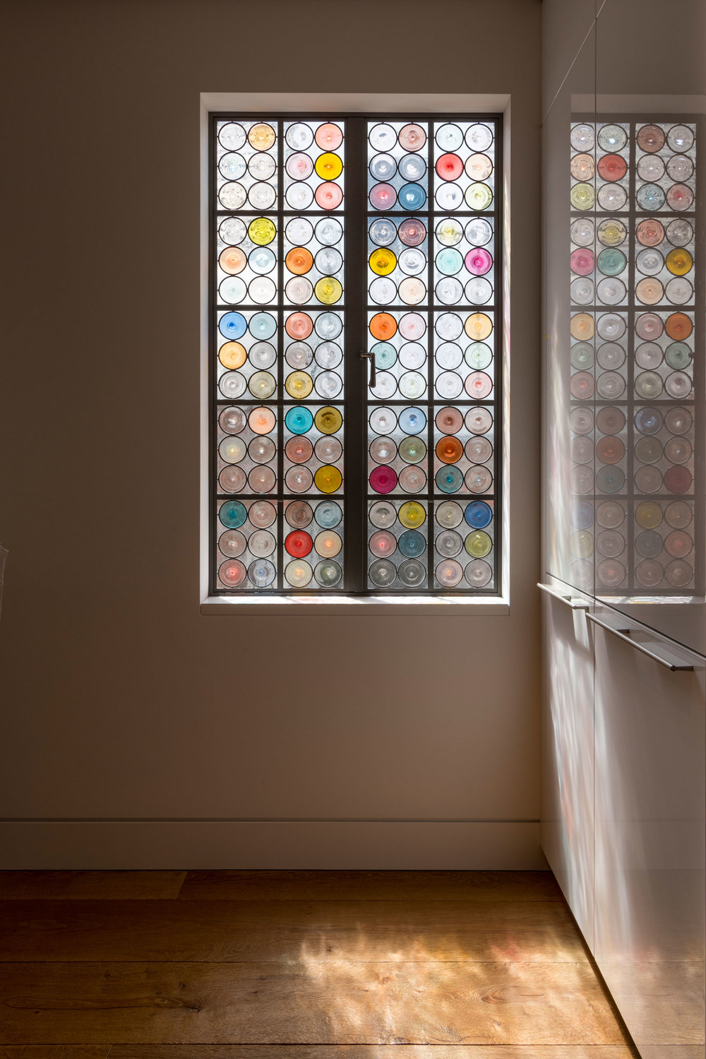 Rondels were the earliest forms to be made and used in the first leaded glass windows 800 years ago. We collaborated with an architecture firm to create a series of 375 light filtering panels that would allow light to enter the space while providing privacy.