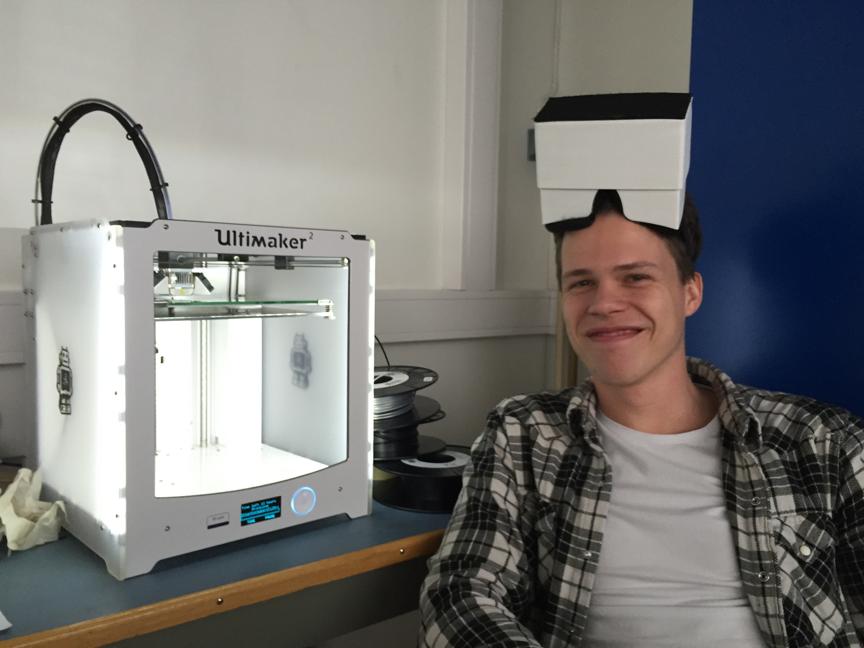 Eirik gliser ved siden av 3D-printeren Ultimaker – tatt på morgenkvisten etter at printeren har jobbet hele natten for oss!