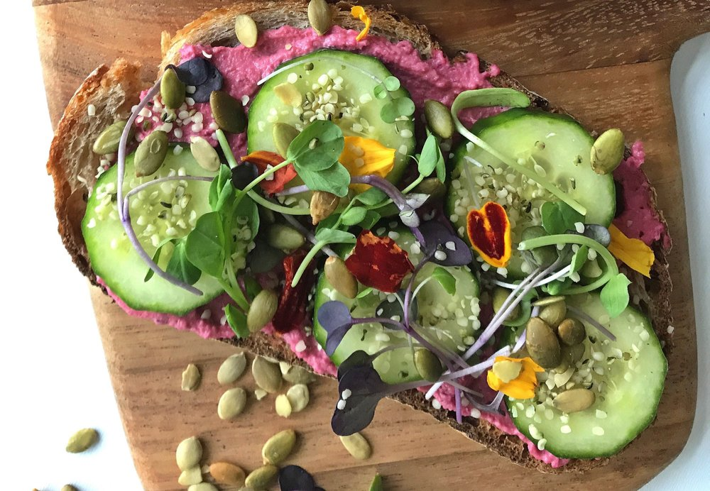BEETROOT HUMMUS ON SOURDOUGH TOAST WITH CUCUMBER, MICROGREENS, PUMPKIN SEEDS & HEMP HEARTS.