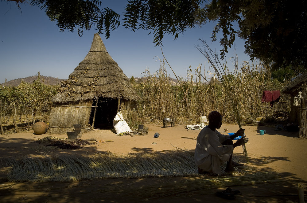 "Sitting under the shade of a tree, in his compound, a refugee makes straw panel used for roof. He sell it for 2000 CFA (4.18 USD). ""Two days are necessary to make a panel. One day to collect the straw out of the bush and one day to make it."" Looking for cash money, the refugies do income activities.   Created on 4 june 2004, Djabal camp sheltered 17.766 persons and 4.681 families in december 2011. It is located 4 kilometers west from Goz Beida, 217 kilometers south from Abeche, 900 kilometers east from N'Djamena the capital and 80 kilometers from the sudanese border."