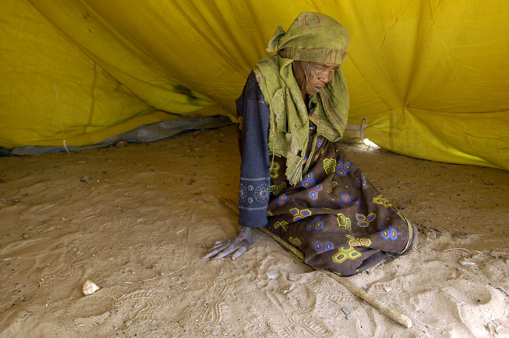 An old, blind refugee in her tent in Kounoungo camp.