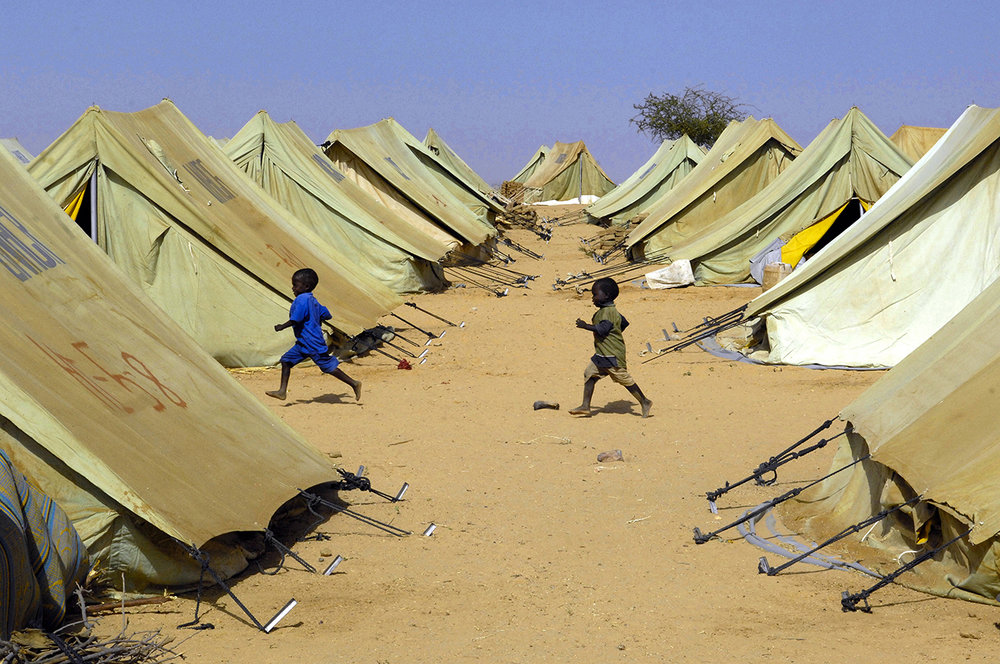 Two newly arrived boys run between tents in Kounougo Camp. The tents are used as temporary shelter until the refugees can build sturdier mud brick huts.