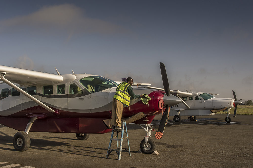Early morning on Arusha airstrip, in northern Tanzania. A maintenance technician prepares a Cessna Grand Caravan, for its first morning flight to the airstrip of Seronera, an hamlet of few houses located in the heart of Seregenti National Parc, in Tanzania.