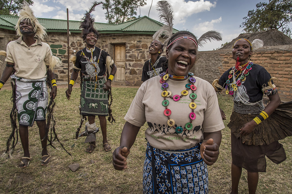 "Members of the group ""Sinduka Cocoba"" interprets the ""Singori"" a welcoming song in the village Nyichoka, about 30 kilometers West of the Serengeti. The object of ""Sinduka Cocoba"" is microcredit in order to allow its members to invest in projects that ensure their subsistence. The only condition: that nature is not affected by the project.  The capital, held in a metal safe in the home of one of them, consists of ""shares"" of 4,000 Tanzanian shillings (about two euros) purchased by the members. The members of the bank meet each Saturday. Debts are then repaid and disbursements made.  Agnes Marongoli (right) with her husband Maro, built a small cultural center with loans. Tourists come to buy handicrafts and listen to the ancient animal myths of the Ikoma tribe."