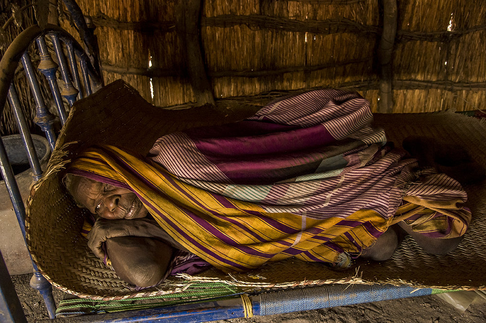 Mourra village, Ouara district, Ouaddaï region. Angoussa AMBOGENE whose age is estimated to be betweenn 90 and 100 years rests in her bed, at home. Her grand- daughter, who helps her to sustain although she is already taking care of more than 20 persons, lives few hundreds meters away. Her ick husband, lives in a different hut, at the end of the street.