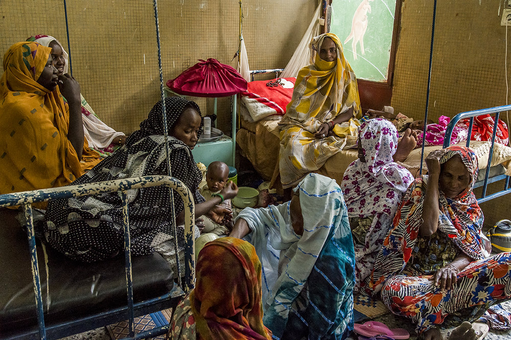 Regional hospital of Abeche, Ouara district. In a dormitory of the Pediatric Section, women who came to visit two friends whose children have been admitted, discuss.