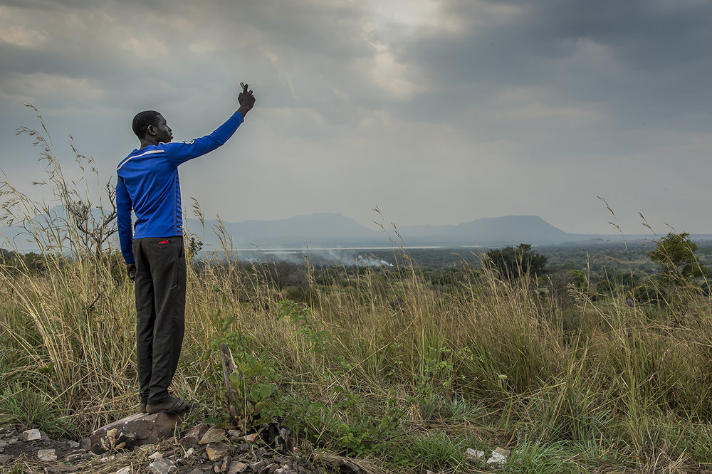 Uganda, Adjumani district, Northern Uganda. A South Sudanese refugee youth tries to get signal on his mobile phone in Nyumanzi refugee settlement. From this hill overlooking the refugee settlements, refugees can sometimes pick up the South Sudanese phone network and make cheaper calls home. November 2014