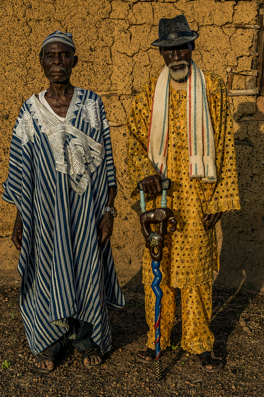 """Village of Gouleako, on the road to the forest of Taï and its national park. An elder, actual village leader, Victor Tere of the Oubi tribe (left in blue) and a friend. """"Formerly we were hunters and went into the forest. The whites took the forest. Now they have to give us back something. """""""