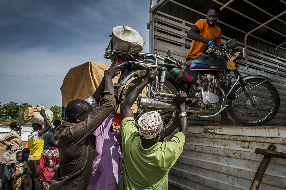 In the Goboro transit center, refugees help one of them to load a moped in a truck that will transport their luggage to the Imvepi reception center. Some manage to flee with minimal planning so that they do not arrive in Uganda totally destitute. From different points of entry along the border between South Sudan and Uganda, the refugees are gathered in transit centers where they are welcomed, fed and as quickly as possible taken by bus to the Imvepi reception two hours drive away.