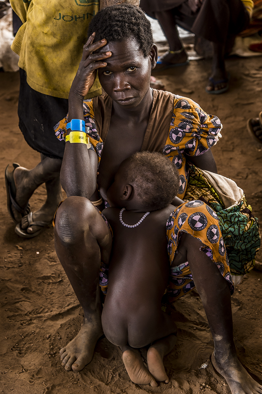 In a transit camp, a mother and her child wait before being taken on a bus that will take them to the Imvepi reception center, a two-hour drive away. She wears a numbered plastic bracelet (yellow for an isolated parent, white for an unaccompanied minor). From different points of entry along the southern Sudanese border, refugees are transported to small transit camps where they are welcomed, fed and identified.