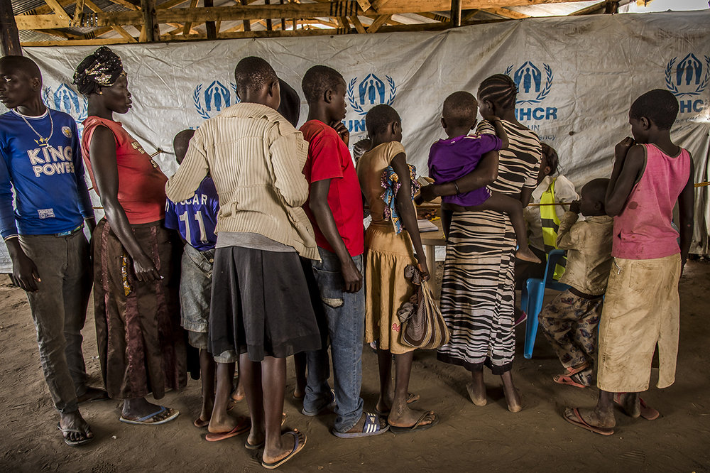 In a transit camp, a group of refugees are quickly registered, interviewed and the families identified and regrouped before being taken on a bus that will take them to the Imvepi reception center, a two-hour drive away. From different points of entry along the southern Sudanese border, refugees are transported to small transit camps where they are welcomed, fed and identified.