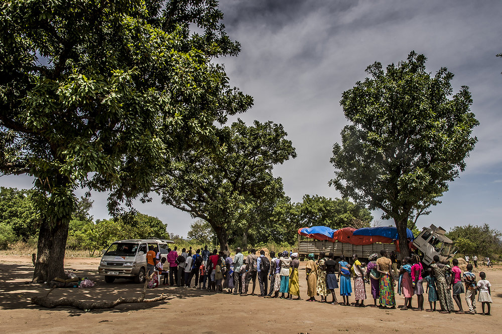 In a transit camp, refugees are queuing to climb in a minibus that will transport them to the main reception center in Imvepi, a two-hour drive away. They were pick up from the border between South Sudan and Uganda. From different points of entry, refugees are gathered in small transit camps, such as this one, where they are offered food, water and where they are quickly treated .
