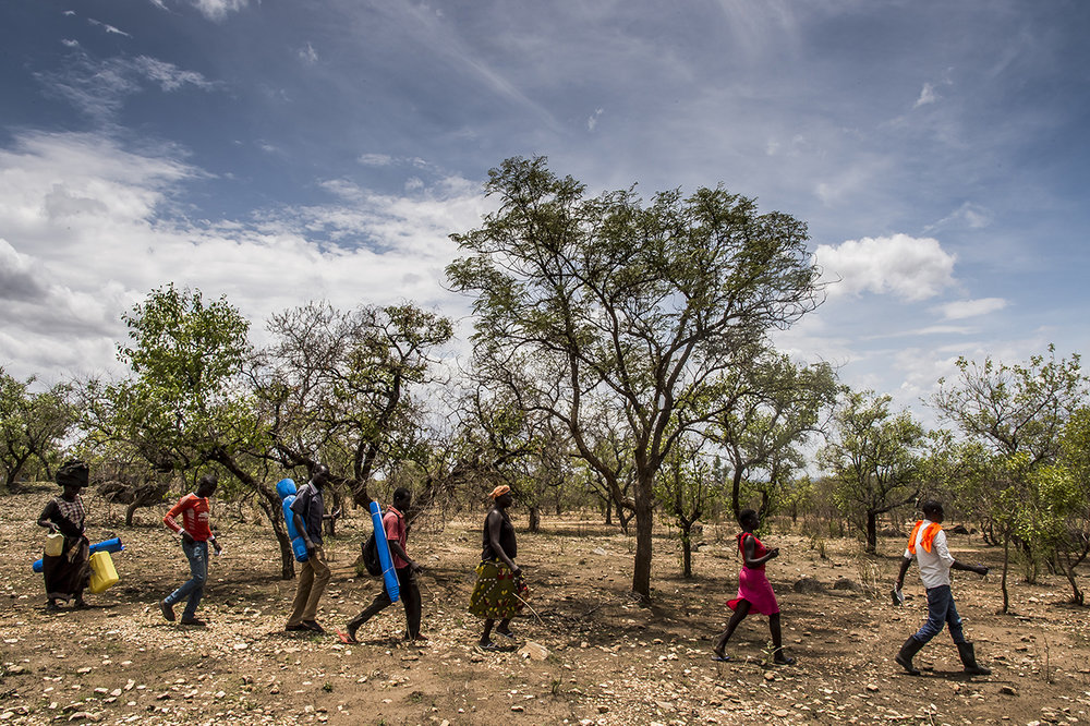 Bidibidi settlement area. An official of the Office of the Prime Minister (OPM) leads the heads of refugee families to the plot of land allocated to them in a wooded and stony area.