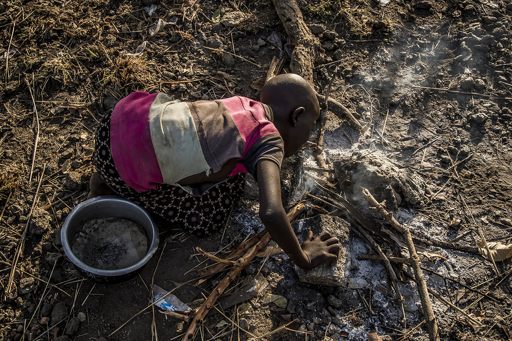 Somewhere in Bidibidi settlement zone, during late afternoon 15 minutes drive from Imvepi reception center, a young South Sudanese refugee girl lights the first fire, to cook the first meal of her family on the family plot. They all have been dropped off with their few belongings in a rocky wooded zone. She hurries. The night will soon come. The first night will be spend in a makeshift tent.