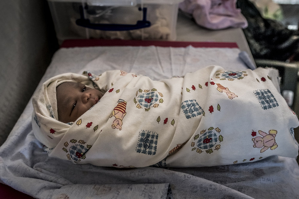 In the settlement area of Bidibidi, at the maternity ward of an NGO's Health Center, the fourth child of Scovia KARABA who has just been born a few minutes earlier. At 28, her mother arrived 7 months earlier, gave birth to his 4th child.