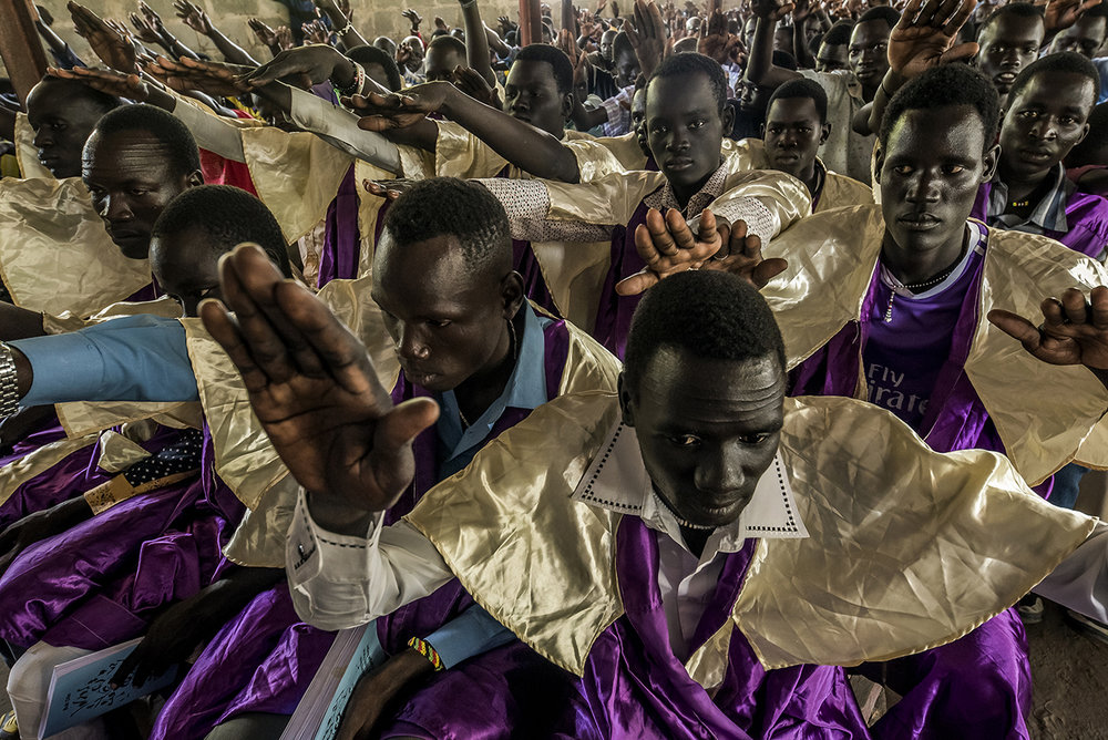 A group of young men respond to a deacon's announcement during Sunday morning religious service in Old Fangak's St. Daniel Camboni Catholic Church, run by the Comboni Missionaries, waving their hands over their heads, cheerfully.