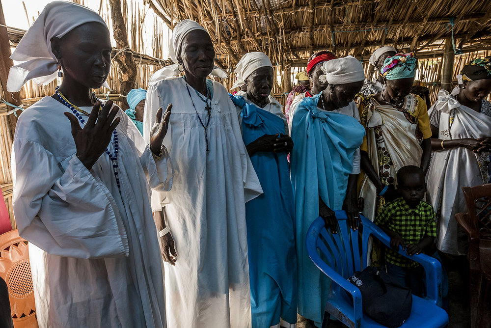 Community elders praying during Sunday morning service in the Old Fangak Presbyterian Church, a large hut with a reed roof dislocated on its ridge. The Presbyterian Church is the main religious organization in the Nuer regions.