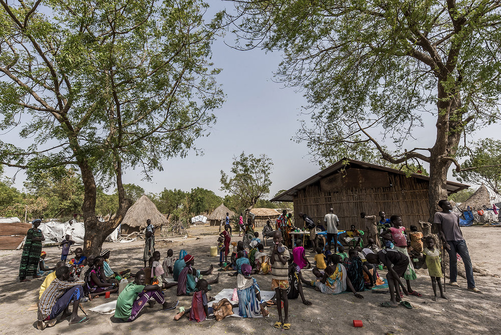 Residents of Old Fangak and IDPs wait to be screened for TB sitting in the shade in front of Tuberculosis Center, a reed-walled hut.