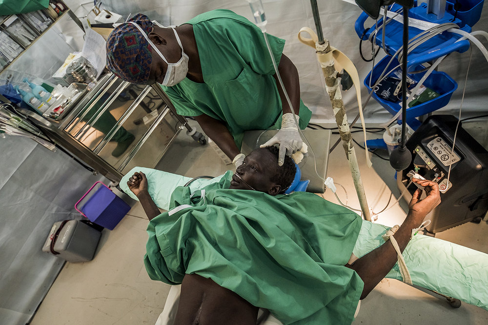 In the operating room built and run by MSF France, an international NGO, Bial Ruoat, about 30 years old, has just been anesthetized. It was brought the day before by 7 people from Khartoum. He says he has paralyzed his legs for 10 days and no longer feels his lower limbs. Worried, he decided to return home to Nuer country. During his stay in Khartoum, he got on a motorcycle taxi. His foot was caught on the shelves or dragged on the ground, while his calf was sticking to the muffler. Feeling no pain, he does not remember anything. He arrives in Old Fangak with severe burns and a big toe, whose bone is raw. He will have to be amputated.  With the possible return of an armed conflict, Old Fangak offers one of the rare sites of access to surgery for the inhabitants of this region of Southern Sudan.