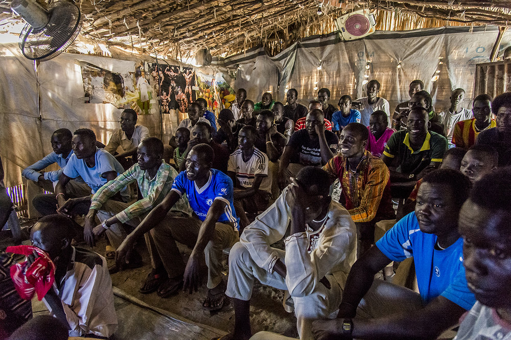 In the Old Fangak market, men watch an English Premiere League football game in a neighborhood cinema for 100 Sudanese pounds ($ 0.77).