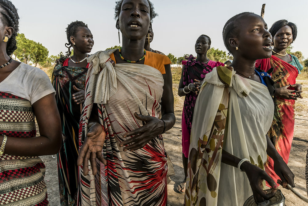 On the edge of Old Fangak town, in a family compound, a group of singers affiliated with the Presbyterian Church rehearse. The Presbyterian Church is the main religious organization in the Nuer regions.